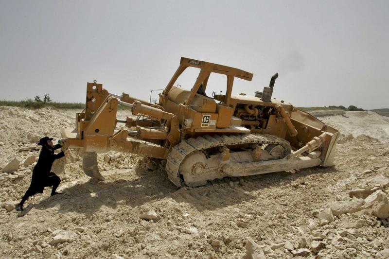 Orthodox and Bulldozer: This photo was selected by Reuters as one of the top 100 photos of the decade