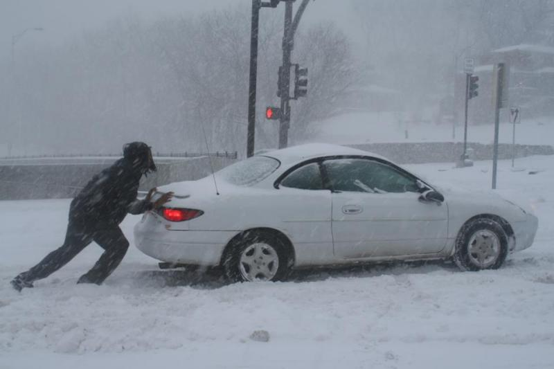 A stalled car gets a push along Troost Avenue.