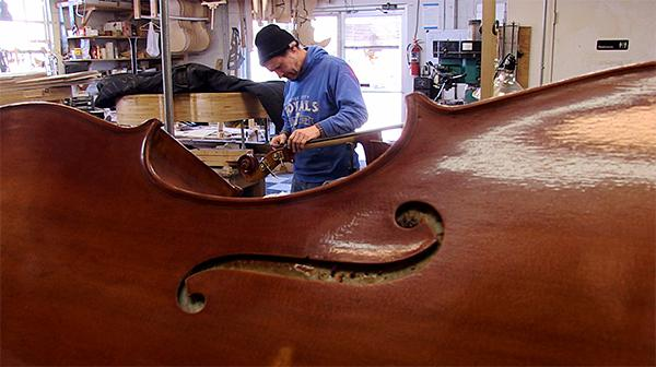 Luthier Alexander Svistunov works on a bass.