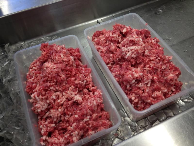 Two of the first large tubs of ground pork that will be added to ingredients and made into sausages.