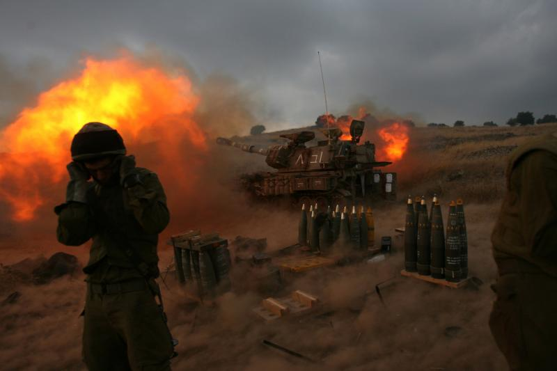 Shooting Under Fire: Israeli soldier standing near a mobile artillery unit as it fires a shell from Zaura, Israel. 2006