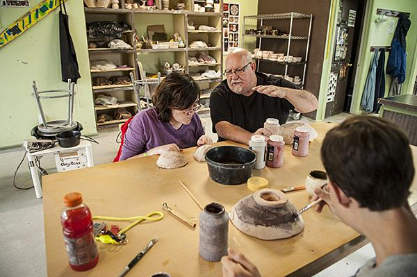 Gathered around the work table, Steven Curtis instructs students on proper glazing techniques.