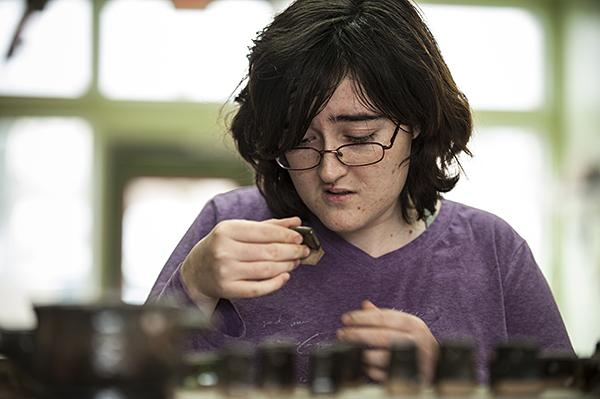 Haley Linnell, 20, of Ottawa, Kans., a student at the Kansas State School for the Blind, carefully selects a glaze for her project.