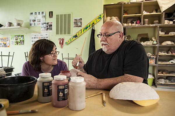 Instructor Steven Curtis helps Linnell get started on a nut shell she is glazing for a school contest.