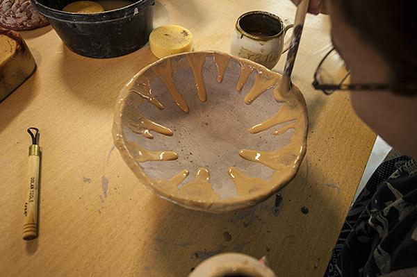 "Emerson enjoys the drips of glaze running down the sides of his bowl. He calls his piece ""Sunbowl."""