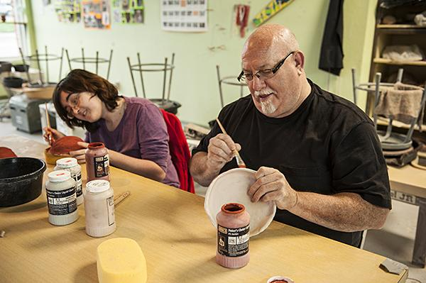 Working side by side with Linnell, Instructor Steven Curtis glazes a bowl for another student.