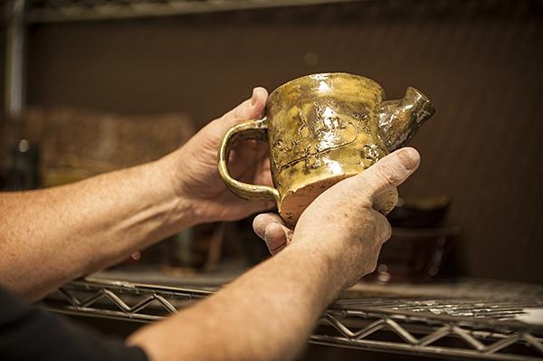 Instructor Steven Curtis holds a glazed student teapot.