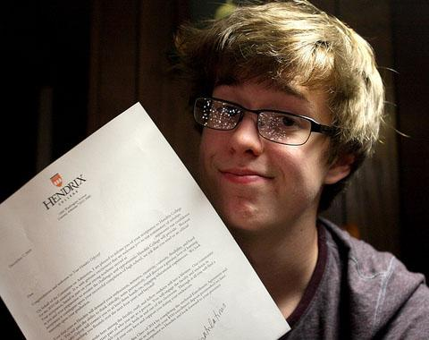 A student shows off his college acceptance letter.