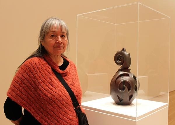 Artist Christine McHorse stands next to a work in the galleries of the Nerman.