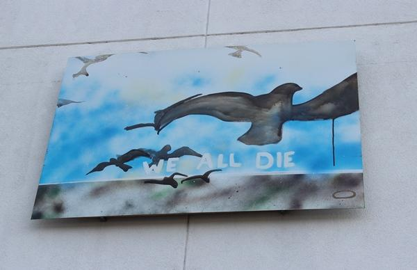 "A David Ford painting on the outside of the building is called ""We All Die."""