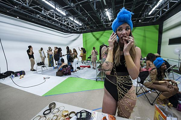 Model Emily Cox, wearing a piece designed by Lane Leavens,  munches on a carrot while speaking to a friend on her cell phone while waiting for the show to begin.