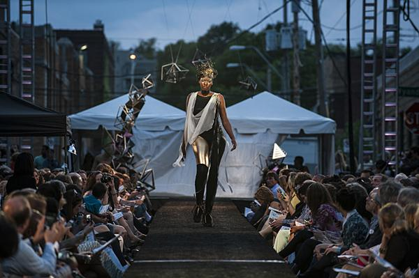 A white scarf shimmers beneath the spotlights as a model wearing Paige Beltowski walks the runway.