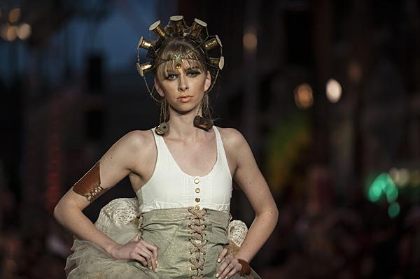 Bedecked in a golden corset and spooled headdress, a model poses in a design by Brock Bryan and Quinn Mahler.