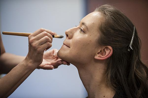 Jodine Romano, a Topeka based-stylist, works behind the scenes applying makeup for Vetter-Drusch as she prepares for her performance.