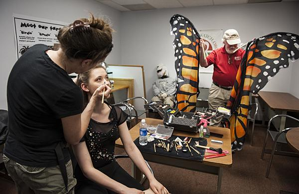 As Romano puts the finishing touches on Vetter-Drusch's makeup, ChipTaylor, Director of Monarch Watch, experiments with the silk monarch wings.