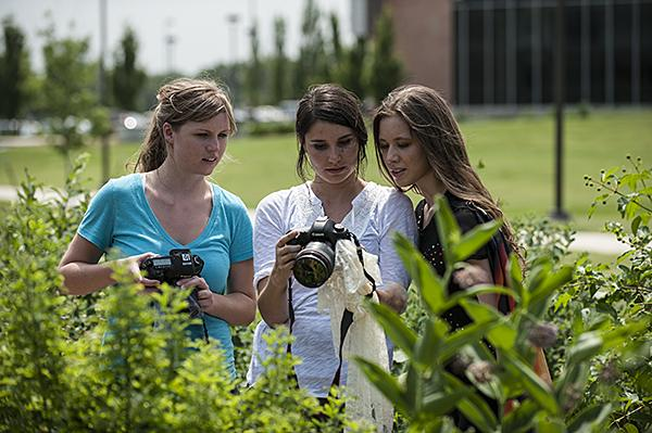 Photographer Jaime Schirmer, (from left) Documentary Filmmaker Gabriella Garcia-Pardo, and Vetter-Drusch look at images.  The three have teamed up to create a photography and film project to raise awareness for monarch habitat.