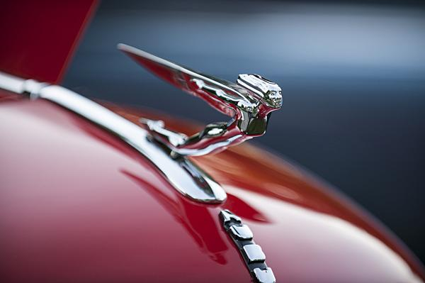 A hood ornament from a 1935 Auburn Model 851, supercharged boattail speedster gleams in the early morning light at at the seventh annual Art of the Car Concours on the grounds of the Kansas City Art Institute.