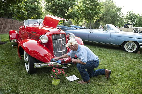 Bob Rohr wipes a streak from the fender of a 1935 Auburn Model 851, supercharged Boattail Speedster.