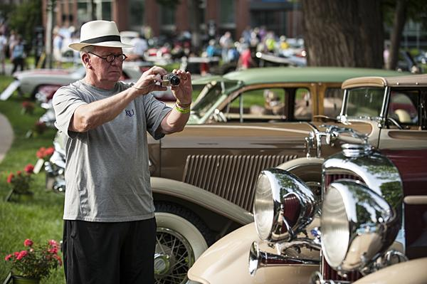 A visitor photographs a 1932 Lincoln KB Touring car.
