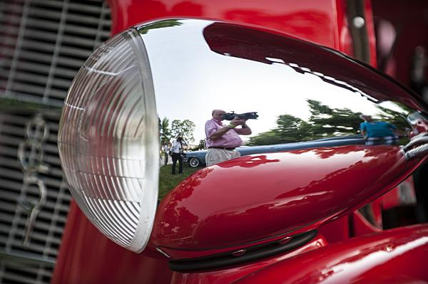 Steve Johnston takes a picture reflected in the curved headlamp of a 1935 Auburn Model 851, supercharged Boattail Speedster.
