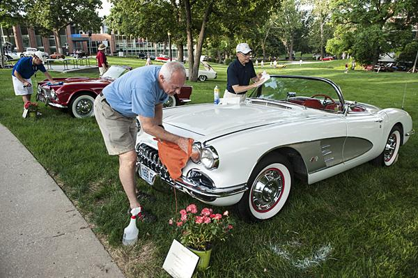 Larry Tomlin and Frank Zilm polish a 1959 Chevrolet Corvette C-1 convertible.