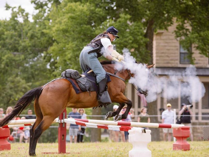 Pfc. Sasha Deas shoots a pistol while jumping a hurdle on her quarterhorse, Chico, during a cavalry demonstration.