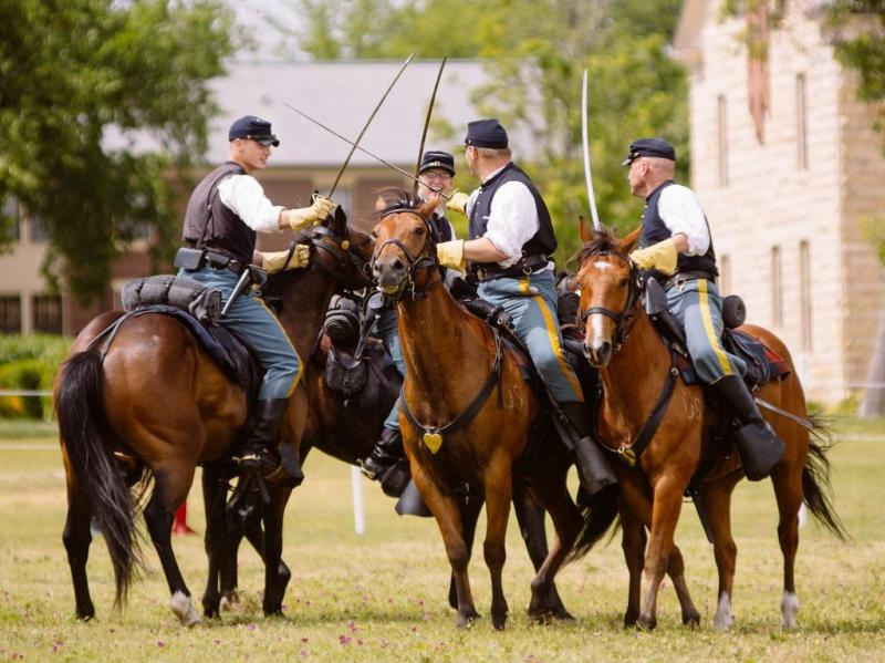 Members of the Commanding General's Mounted Color Guard show off their sword skills during a cavalry demonstration before the Symphony in the Flint Hills on June 15.