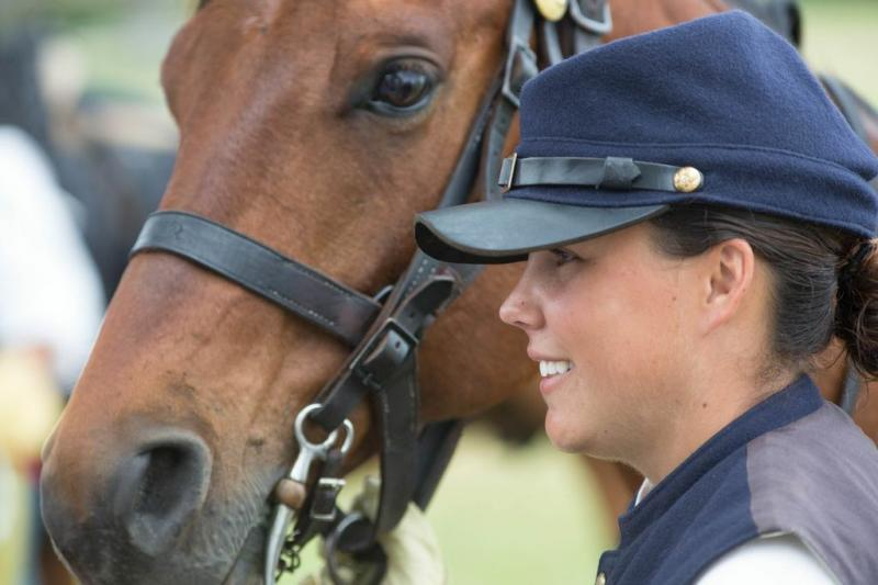 Pfc. Sasha Deas answers questions from the crowd after the cavalry demonstration with her quarterhorse, Chico.