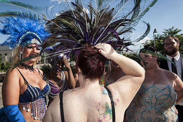Emery Woods keeps her headdress in place as she waits with other members of the burlesque troupe De Allure.