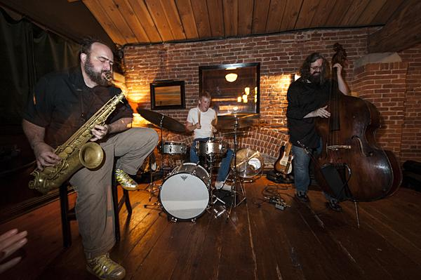 Mark Southerland, on saxophone and Brian Steever on drums, and Jeff Harshbarger on bass, perform as part of an improvisational jazz trio upstairs at Grünauer.