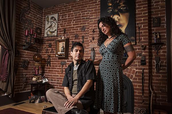 Héctor Casanova Cinderhouse and Renée Cinderhouse pose in front of a wall of items collected over the course of their relationship in their historic Northeast home.
