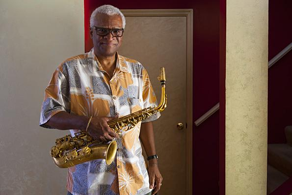 Watson poses with his saxophone in the hallway of his home.