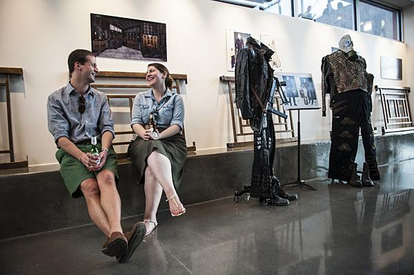 Andrew Wingfield (from left) and Ciana Piraro sit next to costumes on display at the Lyric Opera's first First Friday event.