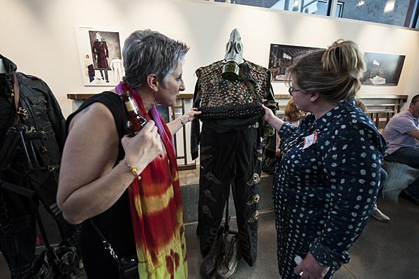 Touching a studded vest on display, Susan Chamberlain (from left) and her friend Lynn Bayes-Weiner admire the workmanship on a costume from the upcoming production of 'The Capulets and the Montagues' by Vincenzo Bellini.