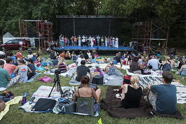 On blankets and lawn chairs, the audience settles in for the show.