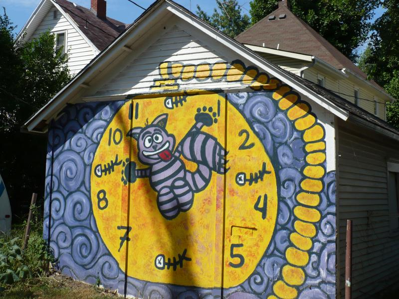 Art Squad muralists painted this cat/racoon on the garage of a neighborhood character who feeds stray cats.
