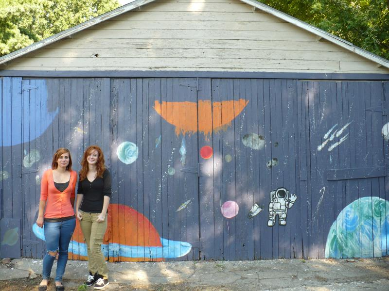 Sisters Amber Finley and Marie Abed pose in front of this space themed Art Squad alleyway mural.