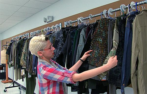 Production Designer Vita Tzykun checks costumes before a fitting session.