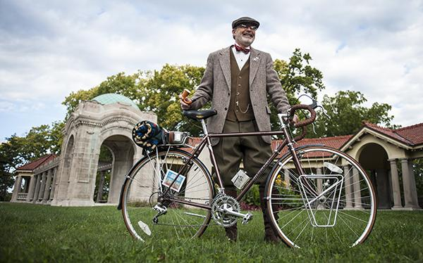 Mark Rainey, founder of the Kansas City Tweed Ride,  poses in a vintage Harris Tweed jacket with his bicycle.