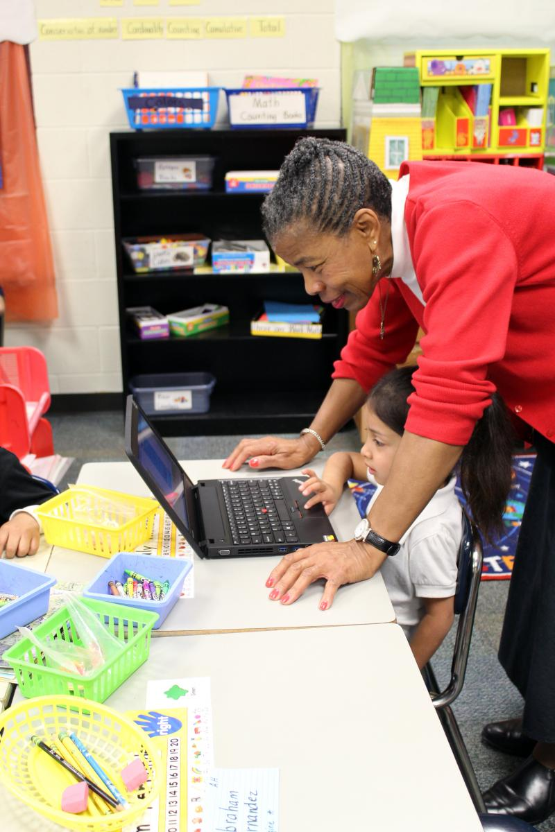 Kindergarten teacher Elowese Jenkins works with a student on a laptop. At James, digital tools are used to accompany learning.