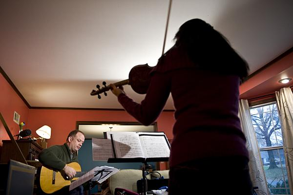 Beau Bledsoe, on guitar, (from left) and  Elizabeth Suh Lane, on violin, work through a piece in the living room of harpsichordist  Elisa Bickers in Overland Park, Kan.