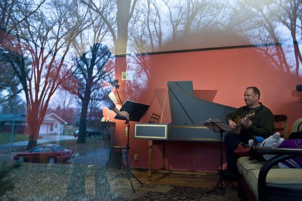 Bare trees on a cold and rainy day are reflected in the window as Elizabeth Suh Lane and Beau Bledsoe practice.
