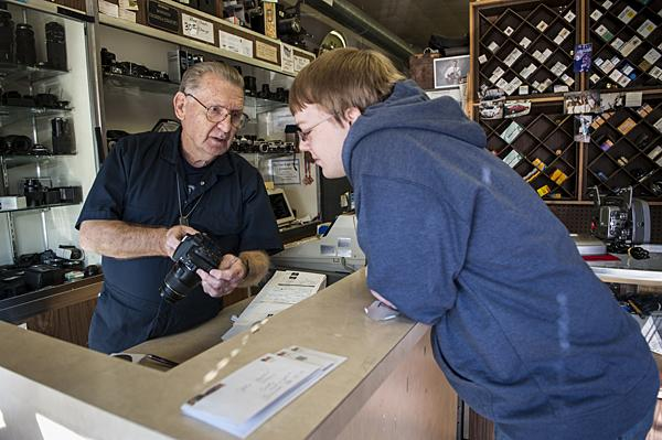 After cleaning the sensor of his digital camera, Clarence Gass talks to customer Zack Becker before returning it to him.