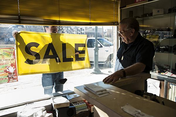 Through the storefront window, Clarence's neighbor Kevin Fullerton of Springboard Creative shows him the sale sign he had made to announce the shop's closing.