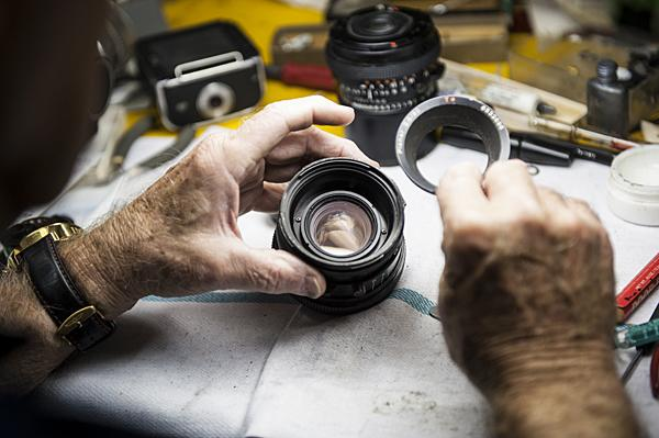 Clarence carefully deconstructs a Hasselblad lens as he prepares to clean it.