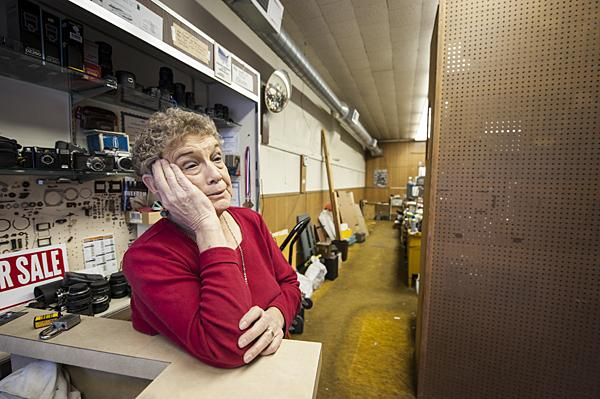 Betty watches from the storefront counter as Clarence loads the trailer with a lifetime of inventory.