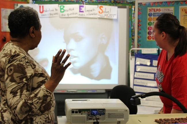 Artist Nedra Bonds shows students a picture of performer Janelle Monae, with assistance from Mrs. Daniels, a Quindaro Elementary School teacher.