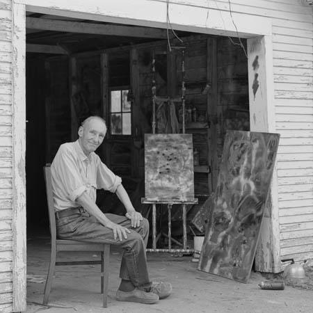 William S. Burroughs with paintings in front of his garage/studio.