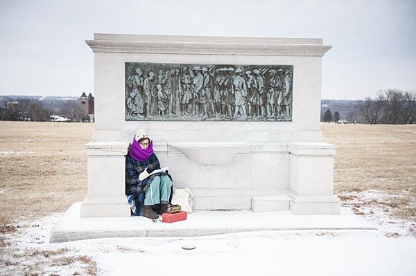 Huddling out of the wind, Telander takes shelter beneath a monument as she sketches.