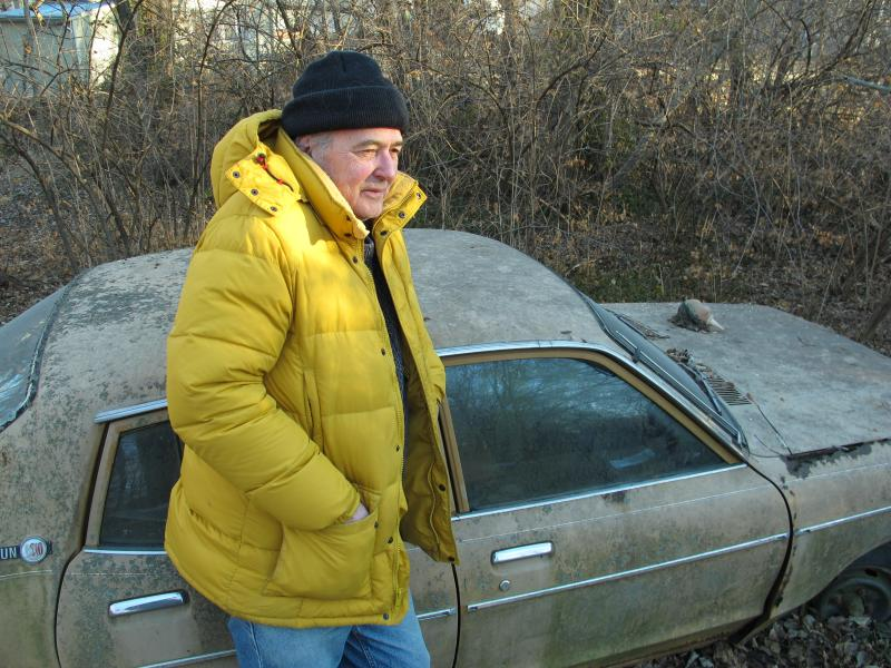 "Poet Jim McCrary, Burroughs' long-time friend, leans on Burroughs' old car, in ""the old man's"" back yard"